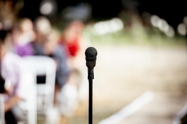 Foto de foco seletivo de um microfone no palco ao ar livre