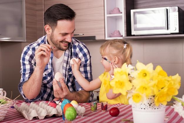 Foto de foco seletivo de um pai e uma filha felizes pintando ovos de páscoa