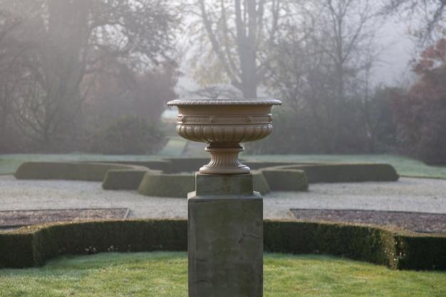 Foto de foco seletivo de um pote de pedra em um pedestal em um parque