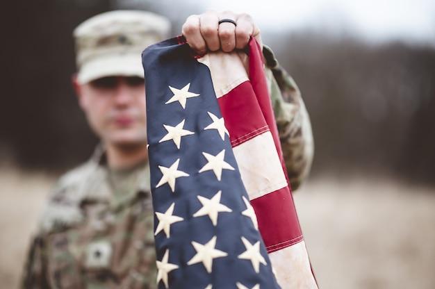 Foto de foco seletivo de um soldado americano segurando a bandeira americana perto da câmera