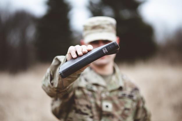 Foto de foco seletivo de um soldado americano segurando a bíblia sagrada perto da câmera