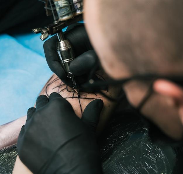 Foto de foco seletivo de um tatuador com luvas pretas criando uma tatuagem no braço de um homem