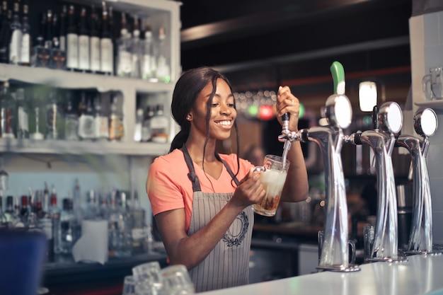 Foto de foco seletivo de uma bartender afro-americana enchendo a cerveja de uma bomba de bar