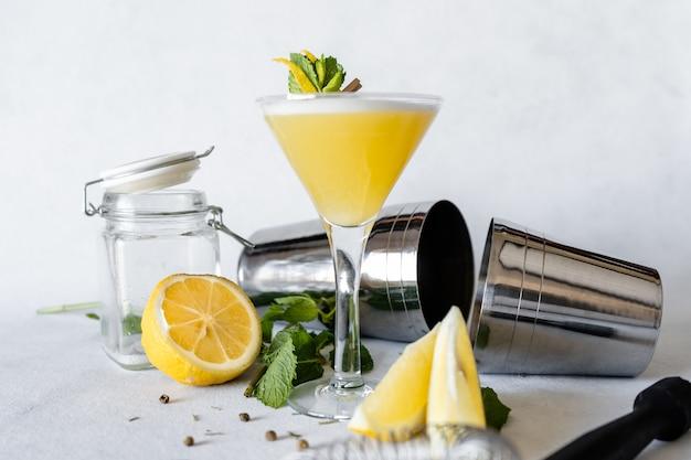 Foto de foco seletivo de uma bebida refrescante decorada com casca de limão e folhas de hortelã