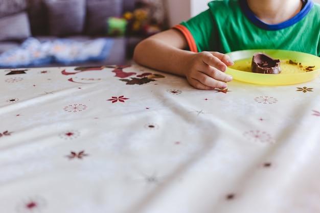 Foto de foco seletivo de uma criança comendo chocolate em uma mesa