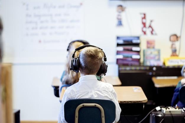 Foto de foco seletivo de uma criança sentada na sala de aula usando fones de ouvido