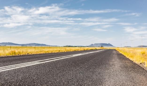 Foto de foco seletivo de uma estrada de asfalto em uma área rural