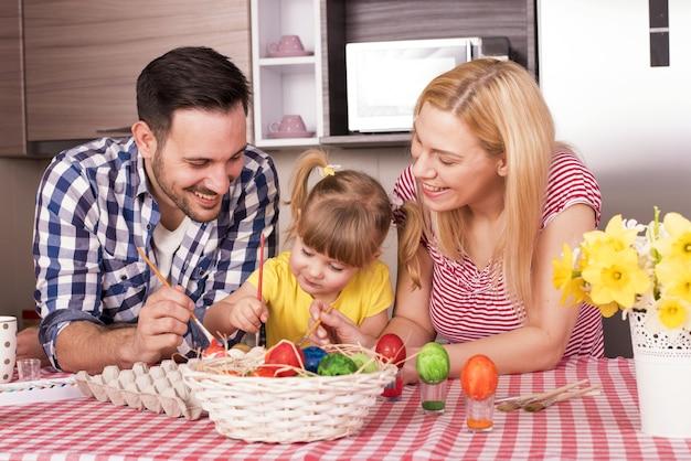 Foto de foco seletivo de uma família feliz pintando ovos de páscoa