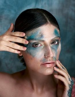 Foto de foco seletivo de uma garota italiana com tinta turquesa no rosto e uma tatuagem na mão