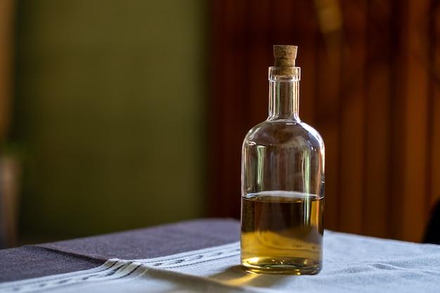 Foto de foco seletivo de uma garrafa de tequila em uma mesa com uma rebarba