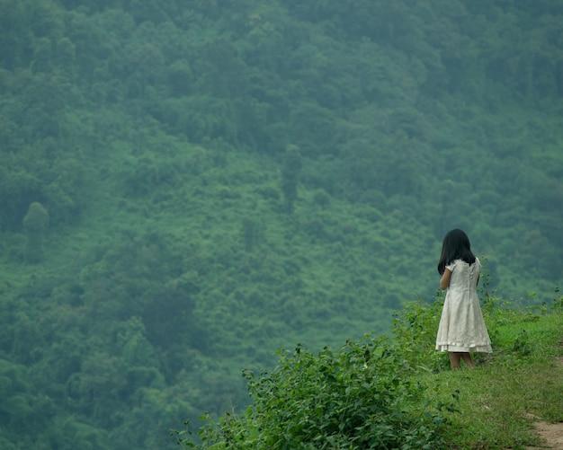 Foto de foco seletivo de uma jovem em pé no topo de um penhasco, olhando para a natureza verde