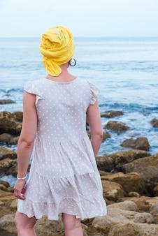 Foto de foco seletivo de uma jovem relaxando à beira-mar