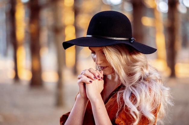 Foto de foco seletivo de uma linda jovem orando em uma floresta
