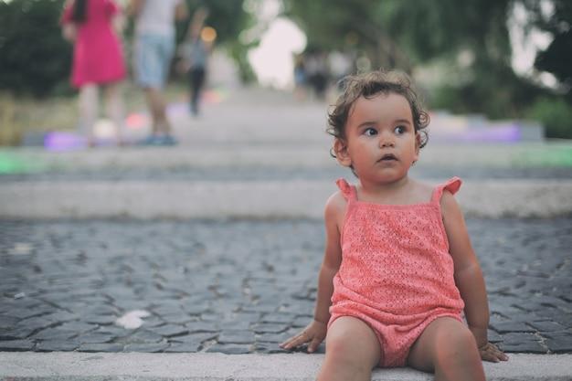 Foto de foco seletivo de uma menina adorável com cabelo encaracolado