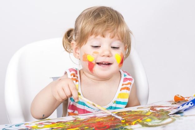 Foto de foco seletivo de uma menina pintando e brincando