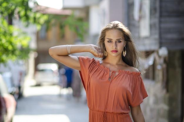 Foto de foco seletivo de uma modelo feminina em um vestido vermelho-laranja em um beco com um fundo desfocado