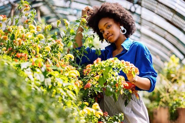 Foto de foco seletivo de uma mulher afro-americana no jardim