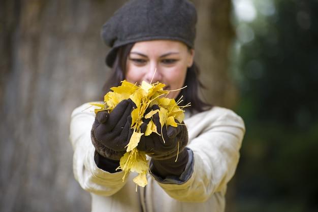 Foto de foco seletivo de uma mulher bonita com chapéu marrom e luvas segurando folhas amarelas no outono
