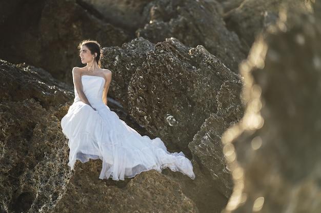 Foto de foco seletivo de uma mulher morena em um vestido branco posando sobre as rochas