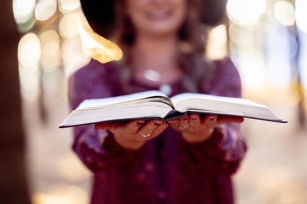 Foto de foco seletivo de uma mulher segurando um livro aberto