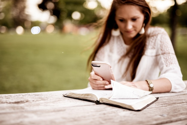 Foto de foco seletivo de uma mulher usando seu smartphone com uma bíblia aberta sobre a mesa