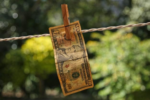 Foto de foco seletivo de uma nota pendurada em um fio com um prendedor de roupa
