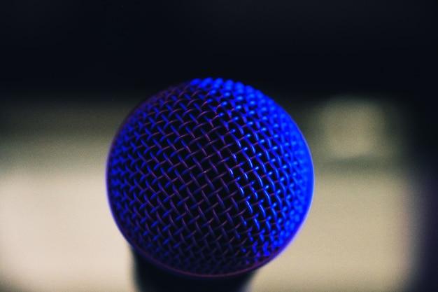 Foto de foco seletivo de uma rede de microfone refletindo a luz azul do palco