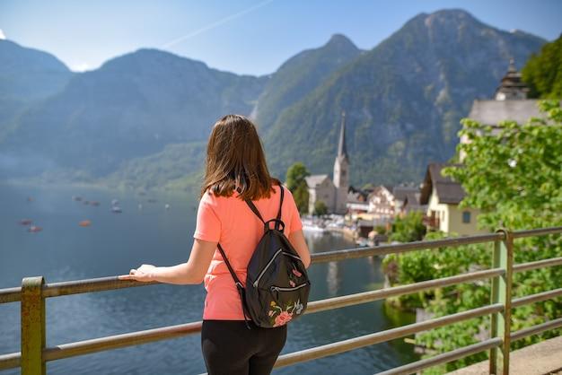 Foto de foco seletivo de uma turista observando uma bela vista do vilarejo de hallstatt, na áustria
