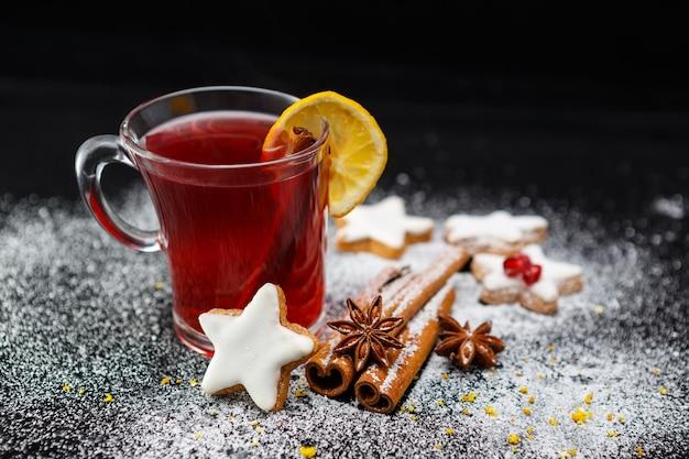 Foto de foco seletivo de uma xícara de chá com biscoitos deliciosos, estrelas de anis e paus de canela