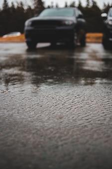 Foto de foco seletivo do veículo estacionado na calçada de concreto