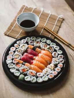 Foto de foco seletivo dos deliciosos rolos de sushi servidos em um prato preto redondo