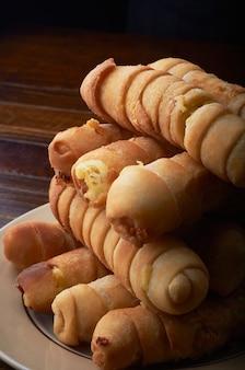 Foto de foco seletivo vertical de corndogs em um prato com um fundo escuro