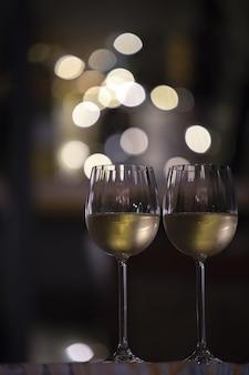 Foto de foco seletivo vertical de dois copos de bebida com as luzes desfocadas ao fundo