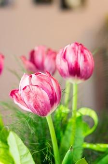 Foto de foco seletivo vertical de três tulipas cor de rosa em um buquê