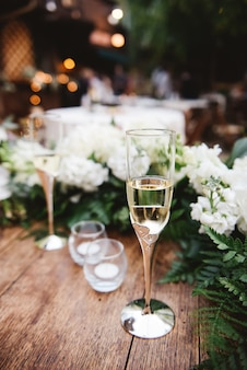 Foto de foco seletivo vertical de uma taça de champanhe em uma superfície de madeira em um casamento
