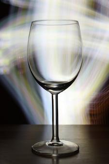 Foto de foco seletivo vertical de uma taça de vinho vazia com luzes desfocadas