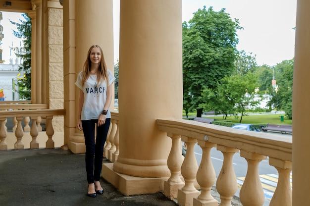 Foto de foco suave da bela jovem entre colunas em camiseta branca.
