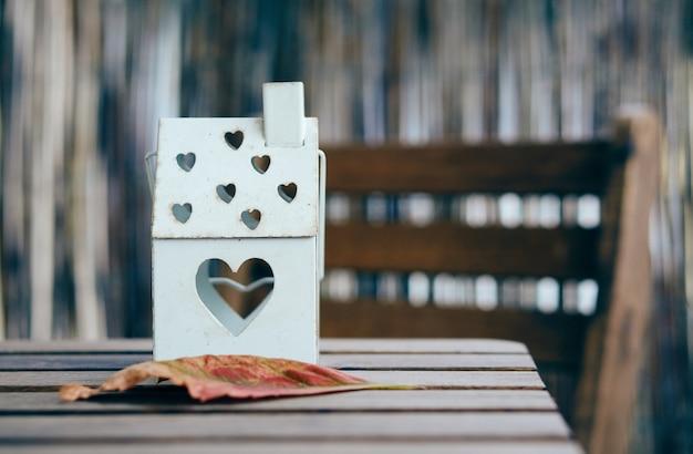 Foto de foco suave de uma lanterna em forma de casa com orifícios de coração em uma mesa de madeira