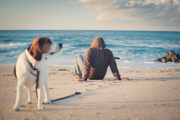 Foto de foco superficial de um homem com uma jaqueta preta sentado em uma praia perto de um cachorro beagle