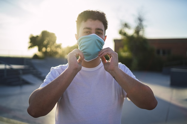 Foto de foco superficial de um homem em uma camisa branca usando uma máscara facial no parque - conceito covid-19