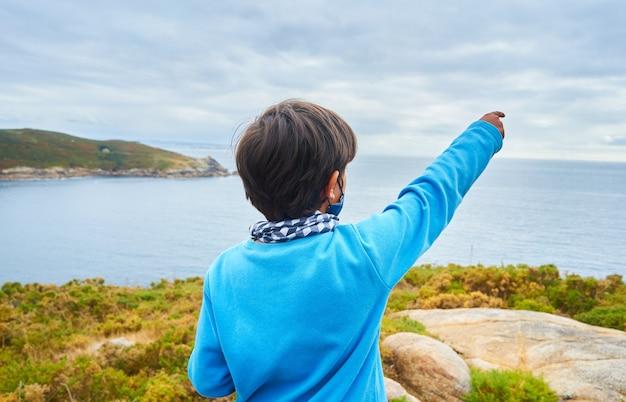 Foto de foco superficial de um menino em um fundo de paisagem marinha