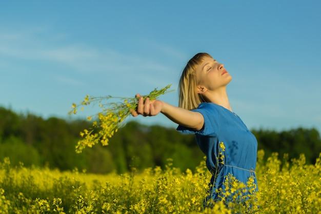 Foto de foco superficial de uma linda mulher caucasiana com um vestido azul, posando em um campo