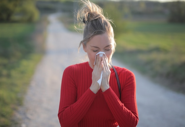 Foto de foco superficial de uma mulher vestindo uma blusa vermelha que está tendo reações alérgicas sazonais