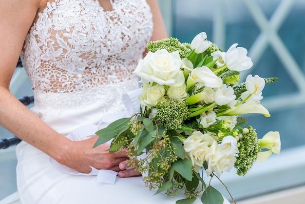 Foto de foco superficial de uma noiva em um vestido de noiva segurando um buquê de flores