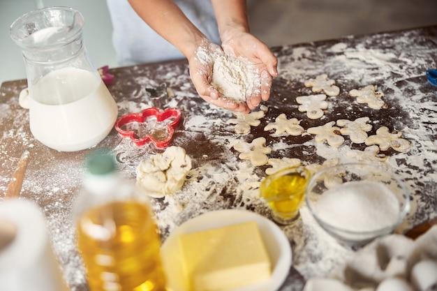 Foto de fragmento de pessoa com um punhado de farinha perto da mesa