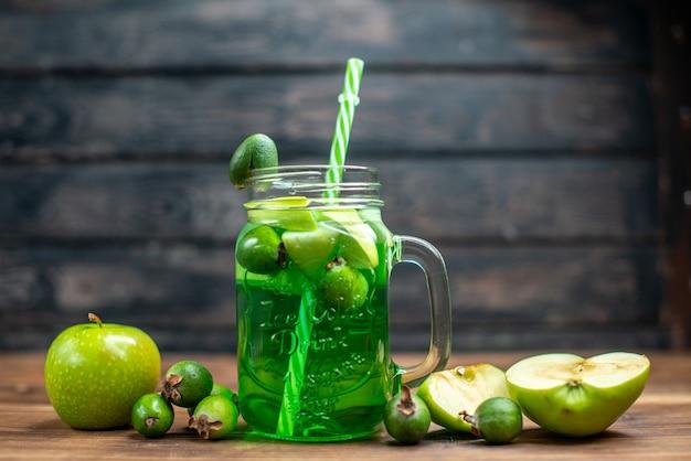 Foto de frente com suco de feijoa fresco dentro da lata com maçãs verdes na foto escura da bebida colorida