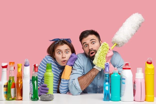 Foto de funcionários de serviço de limpeza assustados olhando para a câmera de forma surpreendente, segurando uma escova de pó, garrafa com líquido químico