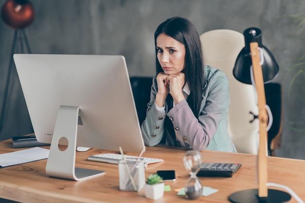 Foto de garota assustada e frustrada economista representante sentar mesa mesa trabalho remoto esperar notificação de perda de emprego executivo usar paletó blazer formal na estação de trabalho