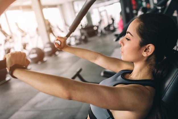 Foto de garota bonita fazendo as flexões na máquina. ela é concentrada e séria.