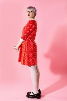 Foto de garota bonitinha bonita com cabelo violeta claro curto, vestido vermelho na parede rosa